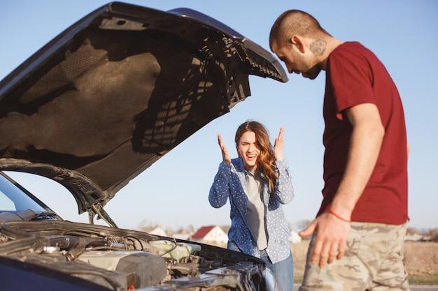 Het paar houdt op weg op als probleem met voertuig. man probeert kapotte auto te repareren, jonge vrouw staat naast hem