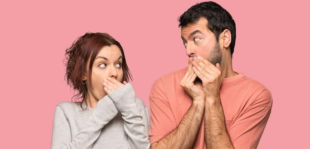 Het paar in valentijnskaartdag die mond behandelen met overhandigt geïsoleerde roze achtergrond