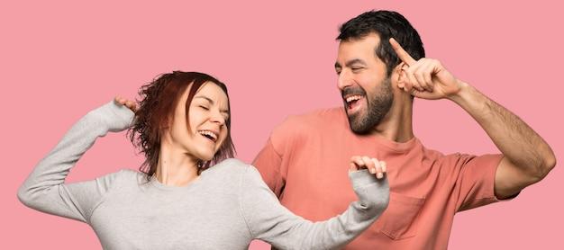 Het paar in valentijnskaartdag geniet van dansend terwijl het luisteren aan muziek op een partij over geïsoleerde roze achtergrond
