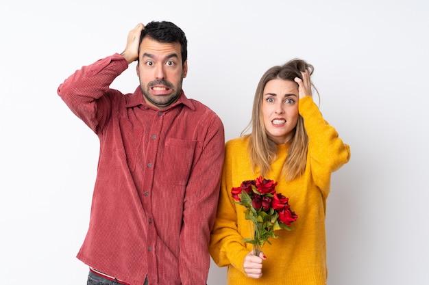 Het paar in valentine day-het houden van bloemen over geïsoleerde muur neemt handen op hoofd omdat migraine heeft