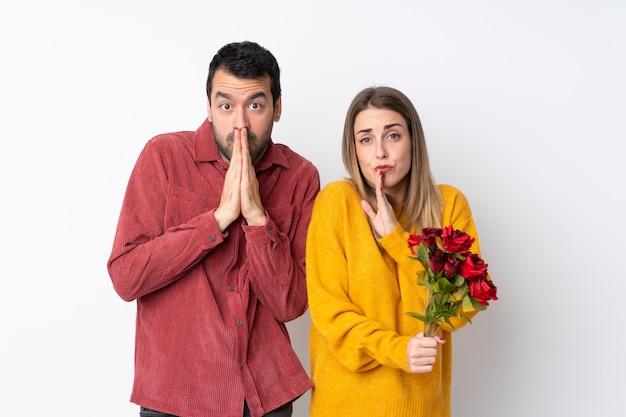 Het paar in valentine day-holdingsbloemen over geïsoleerde muur houdt palm samen. persoon vraagt om iets