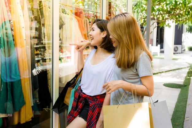 Het paar jonge aziatische vrouwen doet winkelend voor een kleding in een openluchtwandelgalerij in de weekendochtend