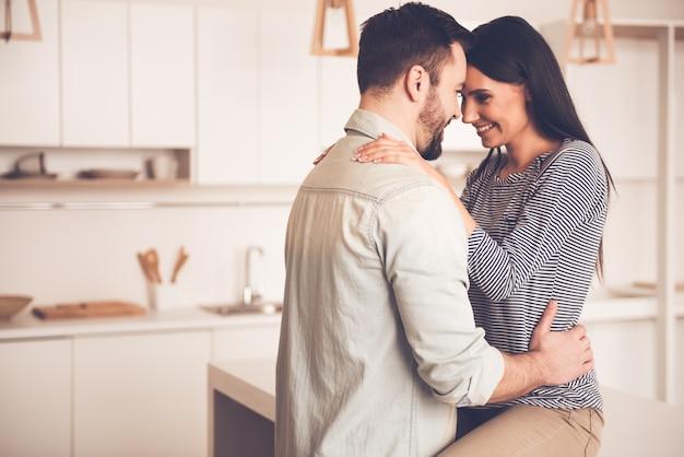 Het paar koestert en glimlacht terwijl het doorbrengen van tijd in keuken
