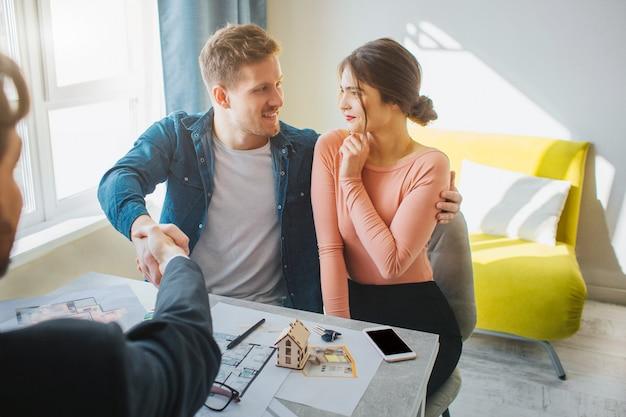 Het paar koopt of huurt samen appartement. ze kijken elkaar aan en glimlachen.