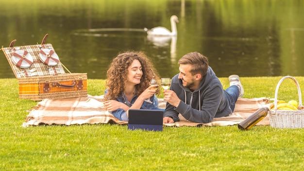 Het paar lag op het gras en drinkt een wijntje op de achtergrond van de rivier