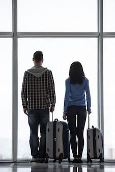 Het paar met koffers kijkt door luchthavenvenster.