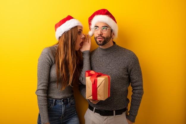 Het paar of de vrienden die giften en het winkelen zakken houden fluisteren roddel ondertoon