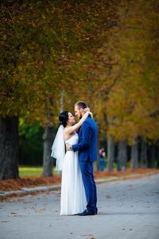 Het paar omarmen op herfst bomen