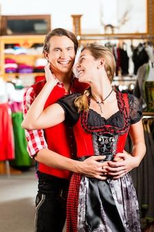 Het paar probeert dirndl of lederhosen in een winkel