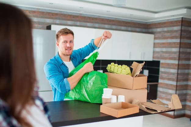 Het paar sorteert afval in de keuken. afval moet worden verzonden voor recycling. er zijn veel recyclebare materialen. op tafel staan plastic, glas, ijzer, papier, oude elektrische apparaten en biologisch afbreekbaar afval.