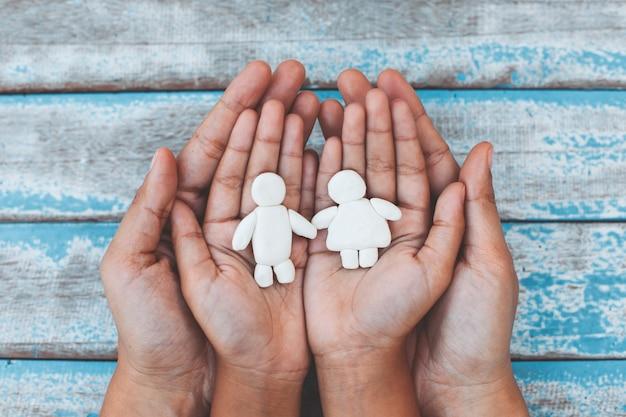 Het paar van de plasticineklei op kind en oudershanden