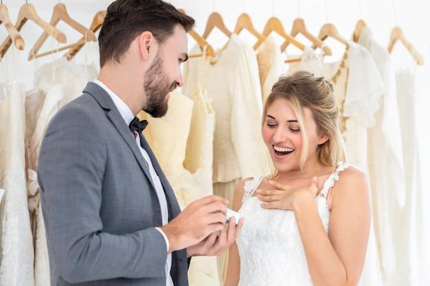 Het paar van kaukasisch, bruidegom geeft huidige bruid in huwelijksstudio.