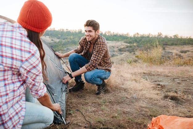 Het paar verzamelt tent op berg