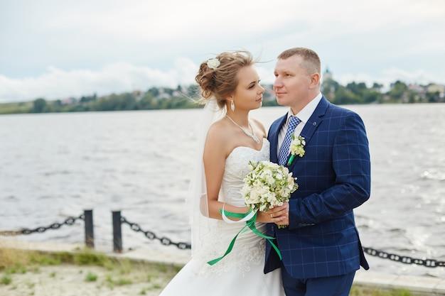 Het paar wed omhelst en kust dichtbij water