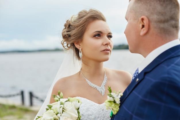 Het paar wed omhelst en kust volgende huizen dichtbij water