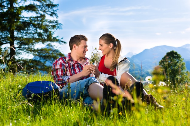 Het paar zit in de weide met berg