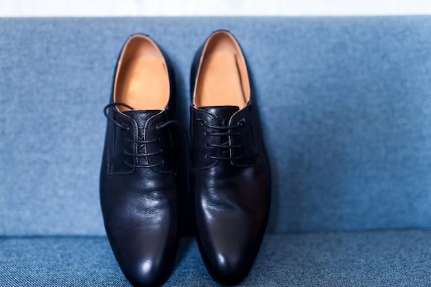 Het paar zwarte lederen schoenen op een blauwe achtergrond. detailopname. bruidegom's ochtend.