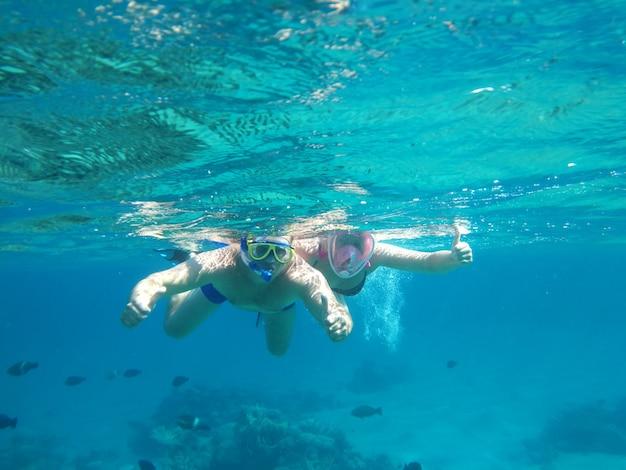 Het paar zwemt onderwater in maskers op het overzees