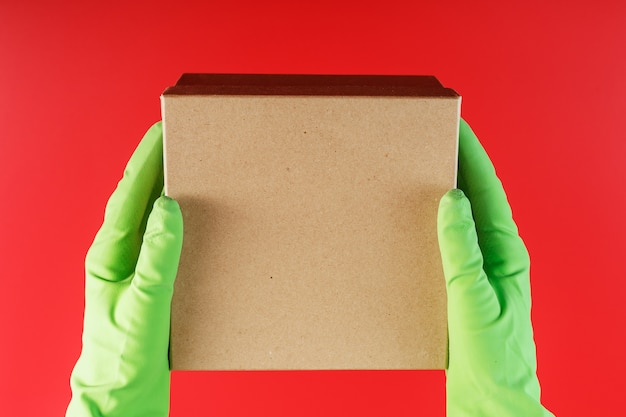Het pakket van de bezorgdienst in de handen met groene rubberen handschoenen op een rode achtergrond.