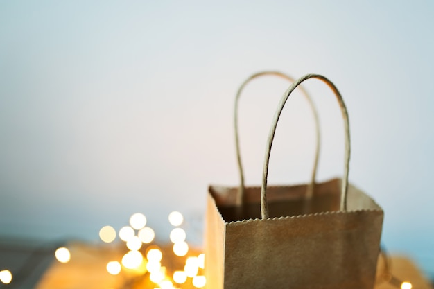 Het pakket van de giftambacht tribunes op de achtergrond van kerstmisslinger en bokeh