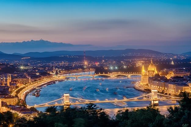 Het panorama van boedapest met het parlement en bruggen tijdens blauwe uurzonsondergang.