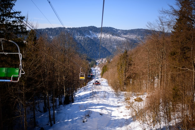 Het panorama van de winterbergen met skihellingen en skiliften op een bewolkte dag