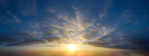 Het panorama van de zonsonderganghemel met wolken en oranje gloed.