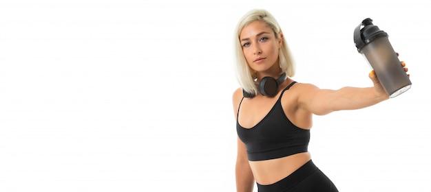 Het panorama van meisje van de sport het kaukasische blonde met oortelefoons doet sporten en drinkt water van sportfles