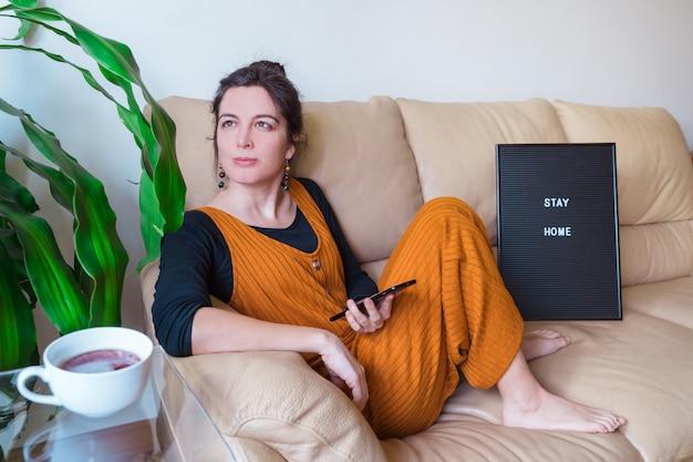 Het panorama van toevallige vrouw zit op de laag roepend een vriend met telefoon. blijf thuis concept. pandemische virusziekte coronavirus covid 19.