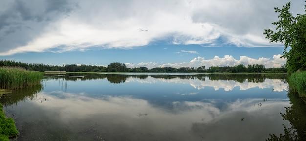 Het panorama weerspiegelde blauwe hemel met witte wolken en bos in een meeroppervlakte