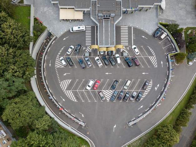 Het panoramische luchtfoto van de drone is strikt boven de parkeerplaats voor auto's met markeringen en hekken voor auto's.