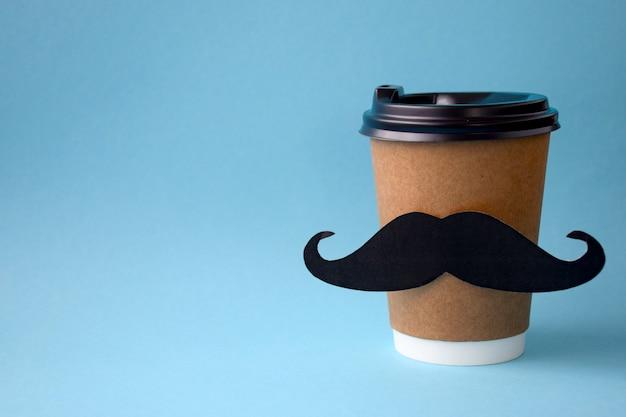 Het papieren kopje warme koffie met papieren snor op blauw