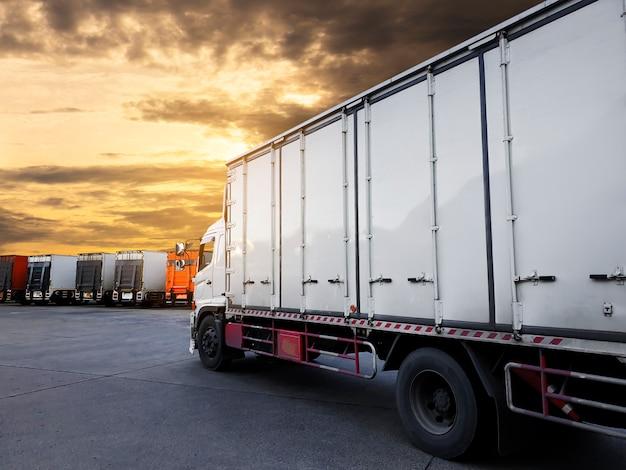 Het parkeren van de vrachtwagenscontainer met zonsonderganghemel