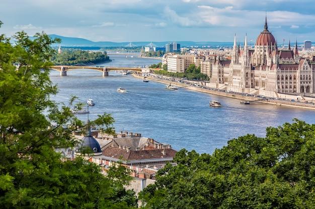 Het parlement en rivieroever in boedapest hongarije met sightseeingsschepen tijdens de zomer zonnige dag met blauwe hemel en wolken
