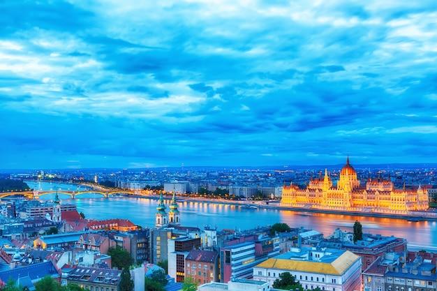 Het parlement en rivieroever in boedapest hongarije tijdens blauwe uurzonsondergang