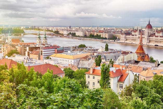 Het parlement en rivieroever in boedapest hongarije tijdens de zomer zonnige dag met blauwe hemel en wolken