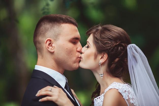 Het pas getrouwde stel zoenen op steegje in het park