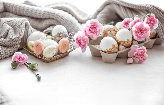 Het pasen-stilleven met paaseieren, verse bloemen en decoratieve elementen sluit omhoog.
