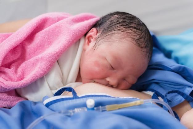 Het pasgeboren babymeisje drinkt eerst moedermelk