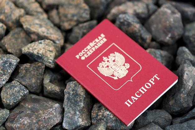Het paspoort van rusland ligt op de rotsen in de straat. verlies van identiteitsbewijs. hoge kwaliteit foto