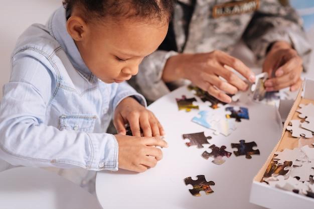 Het past. creatief, ijverig slim meisje dat haar moeder helpt bij het voltooien van een grote puzzel terwijl jij geniet van hun gemeenschappelijke hobby tijdens het weekend thuis