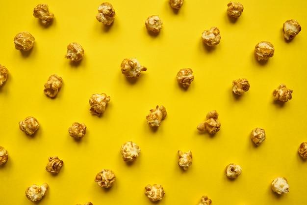 Het patroon van de karamelpopcorn op gele achtergrond. bovenaanzicht, zwart-wit concept