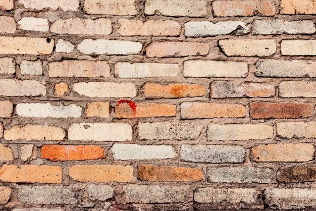 Het patroon van een bakstenen muur met scheuren en krassen