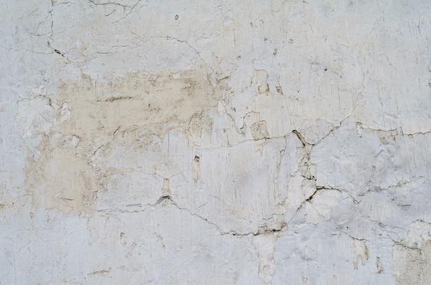 Het patroon van een cement grijze muur met scheuren en gaten