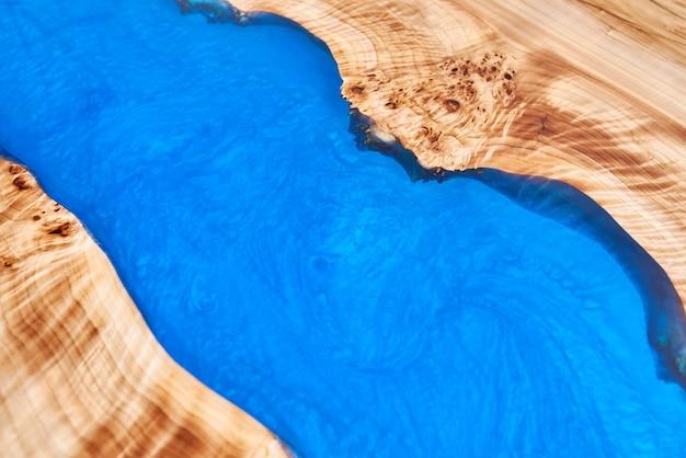 Het patroon van een houten tafel met epoxyhars.