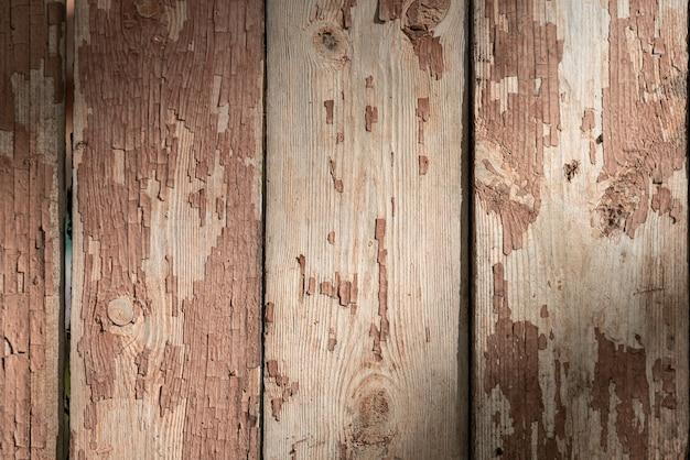 Het patroon van een oud hek. afbladderende verf op het houten oppervlak. het oppervlak wordt verlicht door de zon.