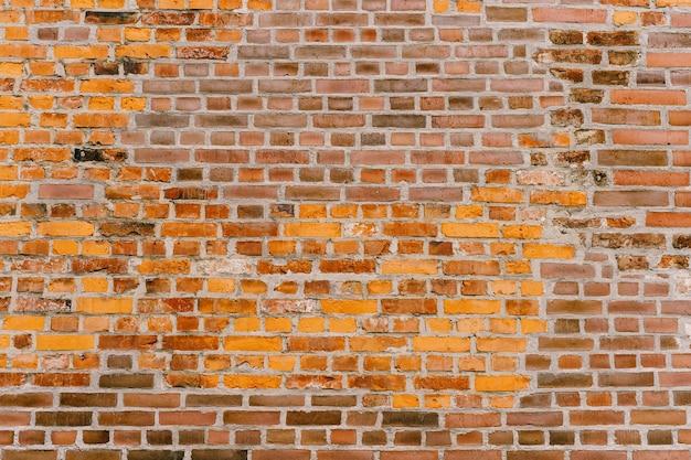 Het patroon van een oude geel-en-bruine bakstenen muur