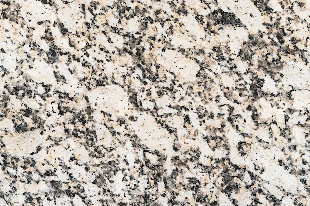 Het patroon van een zwart, wit en zalmkleuren granietoppervlak