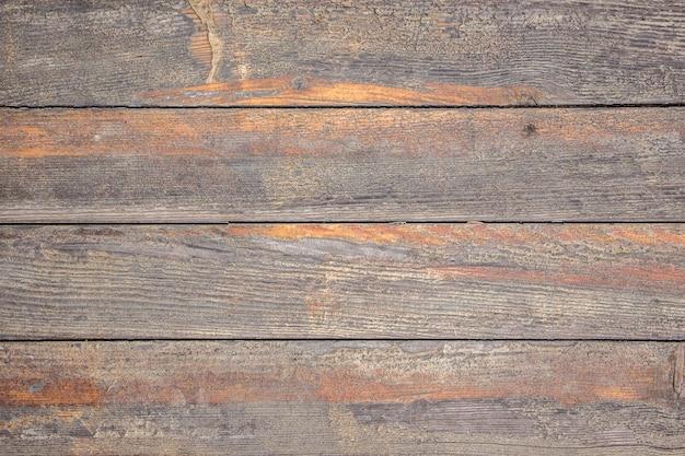 Het patroon van oude houten planken met sporen van afgeveegde oranje verf