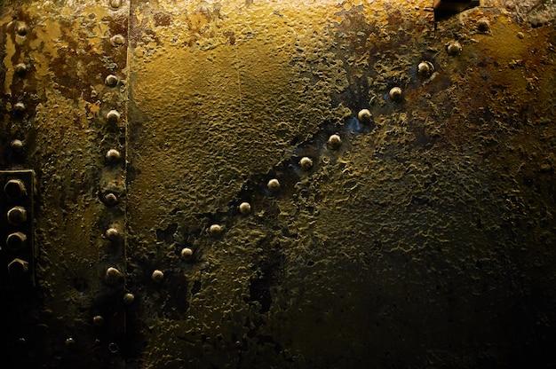 Het patroon van roestig metaal met klinknagels